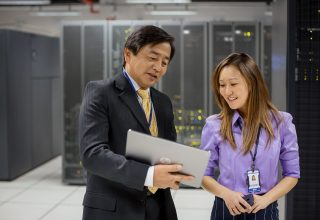 A man and woman using a HP Pro Slate 12 Tablet while working in a data center.